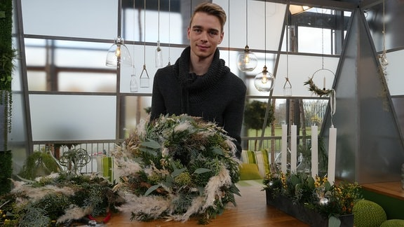 Florist Martin Neumann präsentiert einen bunten Adventskranz aus grünen, braunen und silbernen Zweigen