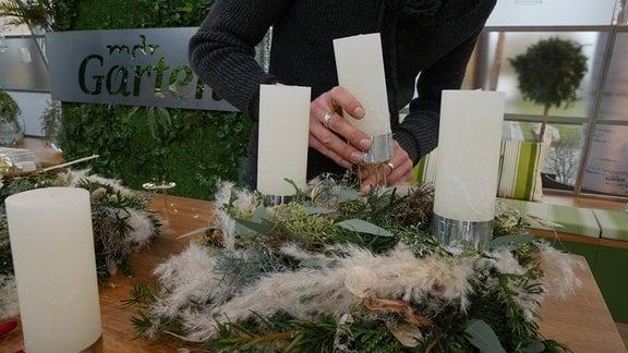 Ein Mann steckt eine Kerze auf einem dreibeinigen Kerzenteller in einen Adventskranz.
