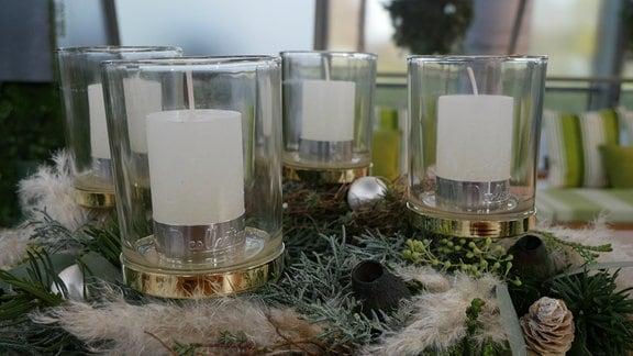 Ein Adventskranz mit Kerzenhaltern aus Glas. Darin kleine, weiße Stumpenkerzen.