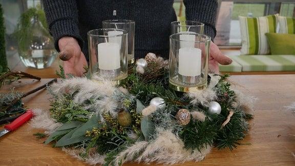Ein Mann präsentiert einen bunt geschmückten Adventskranz mit vier Kerzen.