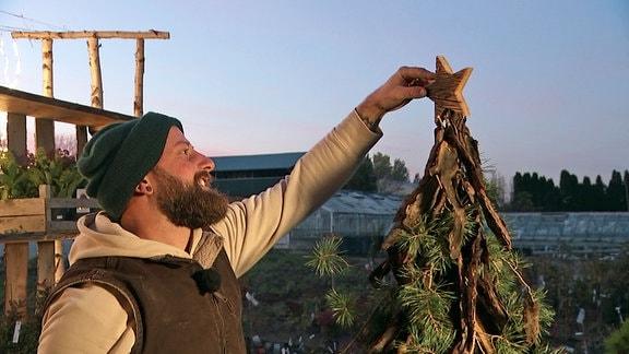 Florist Rocco Wustmann steckt Stern auf wiederverwendbaren Weihnachtsbaum.