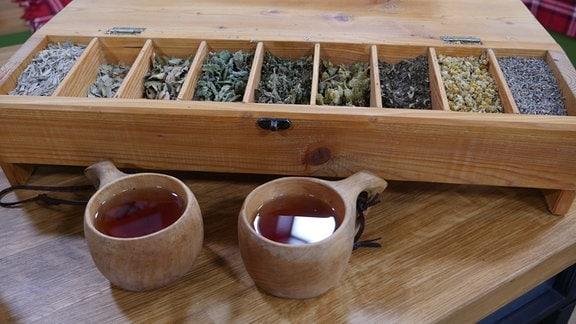 Kräutertee – Auf einem Tisch stehen zwei Holztassen mit Kräutertee, dahinter eine Holzschatulle mit verschiedenen getrocknete Kräutern.