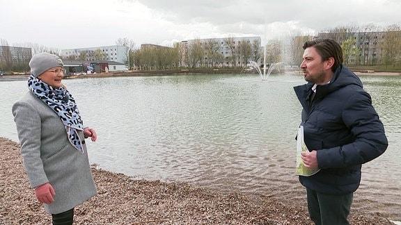 Moderatorin Diana Fritzsche-Grimmig und Gartenamtsleiter Sascha Döll mit einem Plan an einem künstlichen See