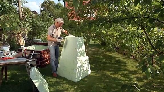 Mann baut ein einem Garten eine Winterhaube für Pflanzen