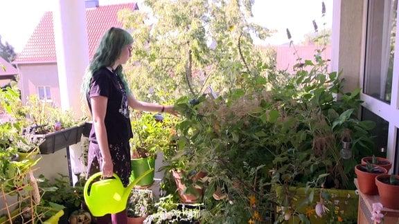 Frau gießt Blumen auf Balkon