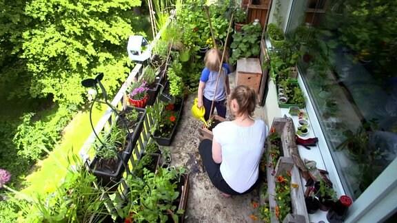 Frau und Kind gärtnern auf einem Balkon