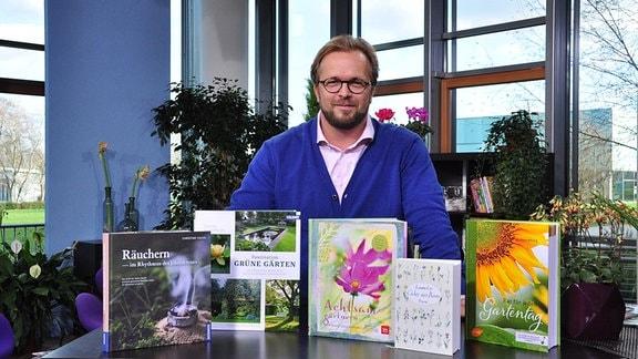 ein Mann steht hinter einem Tisch auf dem verschiedene Bücher präsentiert werden