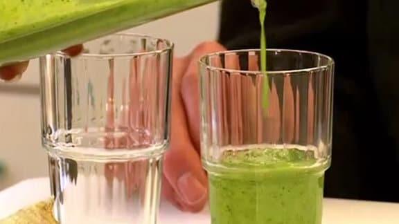 Eine grüne dicke Flüssigkeit wird in ein Glas gegossen.