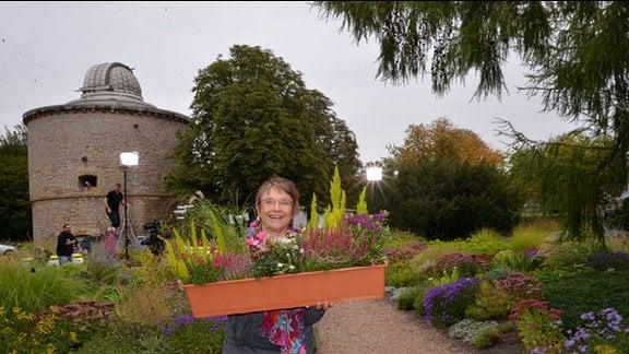 Christel Miller von der Gärtnerei Gruschwitz in Neustadt in Sachsen hat einen Blumentopf in der Hand