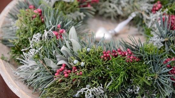 Weihnachtskranz mit Tanne und Kräutern. Besonders schön sehen die rosaroten Pfefferkörner aus, die regelmäßig verteilt sind.