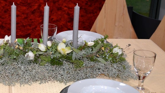 Auf einem gedeckten Tisch liegt eine längliche Weihnachtdeko mit grauen Kerzen, Christrosen und verschiedenen Kräutern und Tanne.