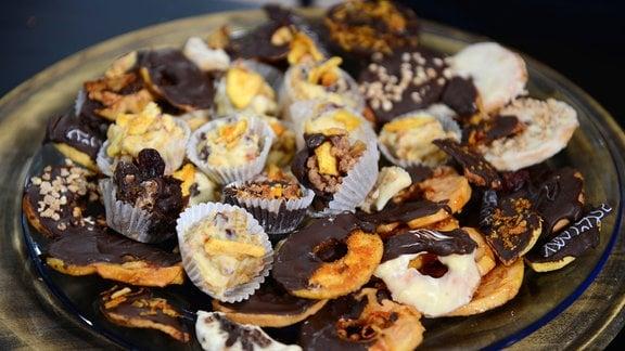 Apfelringe mit dunkler und weißer Schokolade verziert, liegen auf einem Teller.