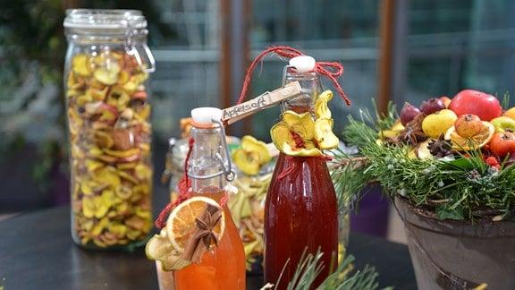 Auf einem Tisch stehen Flaschen mit Apfelsaft- und Sirup, getrocknete Apfelringe sind in großen Gläsern aufbewahrt.