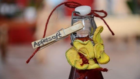 An einer Flasche mit Schnappverschluss klemmt eine Klammer mit der Beschriftung Apfelsaft. Am Flaschenhals wurden getrocknete Äpfel als Dekoration angebracht.