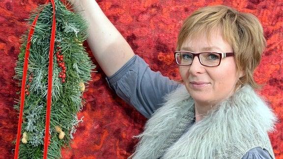 Eine Frau hält einen Tropfenförmigen Weihnachtsschmuck in der Hand