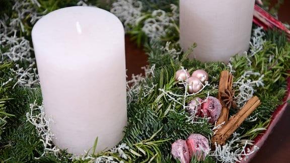 Weihnachtskranz mit großen weißen Kerzen. Als Schmuck wurden zartrosa Kugeln, Äste der Stacheldrahtpflanze und Zimtstangen verwendet.