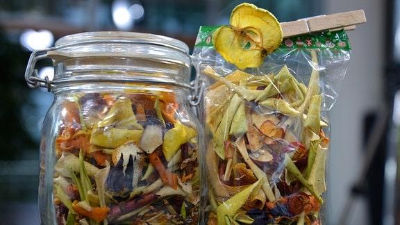 In einer Tüte und einem Glas werden verschiedene Blüten und getrocknete Schalen von Äpfeln und Orangen aufbewahrt.