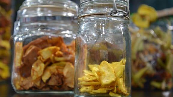 Verschiedene Gläser mit getrockneten Äpfeln stehen auf einem Tisch.