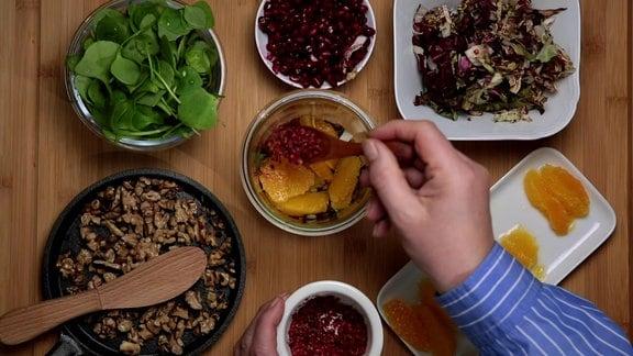 In einem Glas wird Salat mit etwa münzgroßen, hellgrünen Portulakblättern, in Streifen geschnittenem Radicchio, filetierten Orangen, Granatapfelkernen und gerösteten Walnüssen angerichtet und mit einem braun-orangefarbenen Dressing übergossen