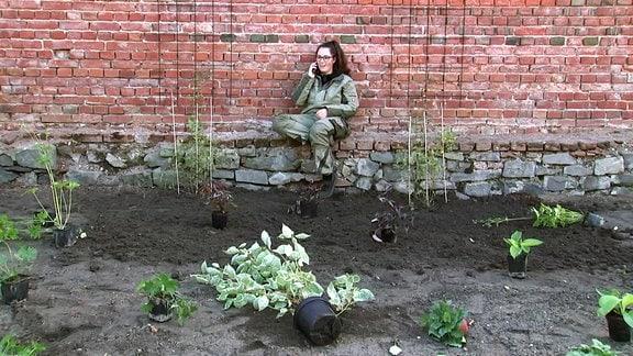 Eine junge Frau in Arbeitskleidung lehnt an einer großen Ziegelsteinmauer vor der ein Beet ist