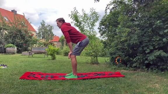 Ein Mann steht mit leicht gebeugten Beinen und den Händen auf den Knien auf einer Decke in einem Garten.