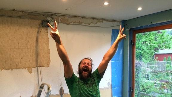 Frank Krause steht erfreut mit hochgerissenen Armen in einer renovierungsbedürftigen Gartenlaube