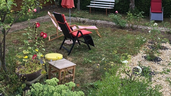 Winzige Rasenfläche in einem Kleingarten mit zwei Liegestühlen und Sonnenschirm