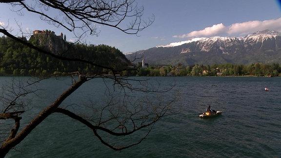 Bleder See mit Ruderboot und Alpen