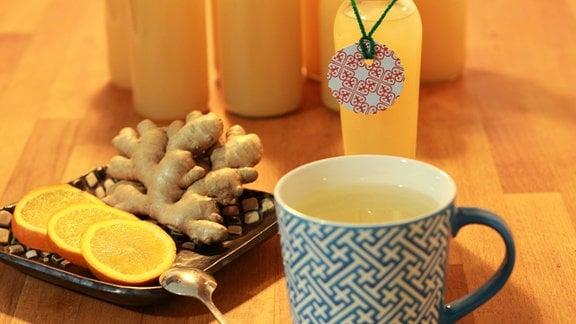 Flaschen voller gelber Flüssigkeit, eine Tasse mit Getränk, ein Teller mit Ingwer und Orangenscheiben