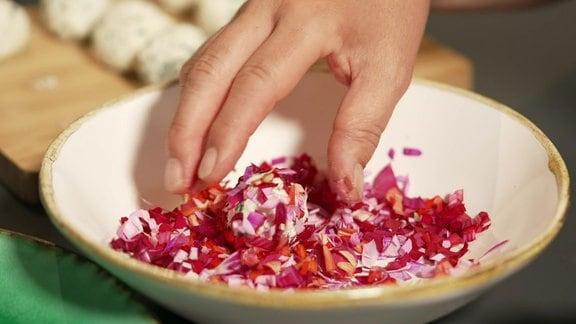 Frischkäse-Bällchen werden in zerkleinerten Dahlienblüten gewälzt