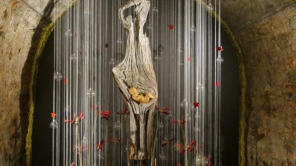 Große Holzwurzel mit Babyfigur in der Ausstellung Florales zur Weihnachtszeit im Domfelsenkeller Erfurt