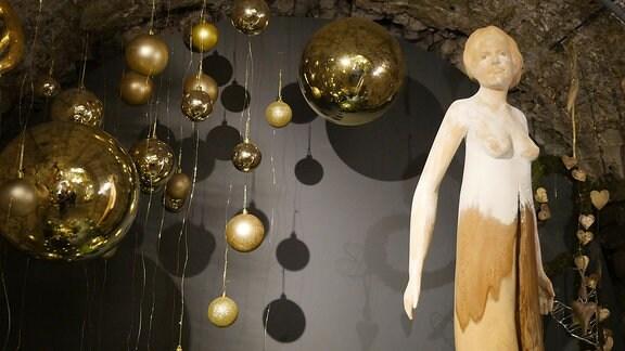 Nackte Frauenfigur aus Holz und goldene Weihnachtskugeln in der Ausstellung Florales zur Weihnachtszeit im Domfelsenkeller Erfurt