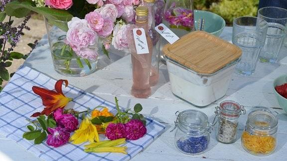 Auf einem Tisch liegen viele Blüten und Produkte, die man aus den Blüten herstellen kann, zum Besipiel Salz, Sirup und Quark.