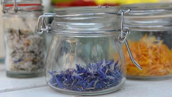 In einem Glas sind getrocknete blaue und gelbe Blütenblätter