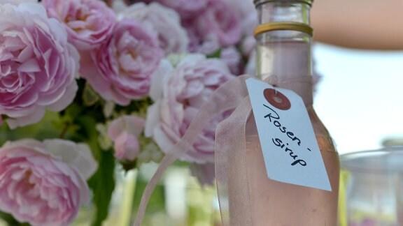 Eine Flasche mit einer Rosa Flüssigkeit und einem kleinen Schild auf dem Rosensirup steht.