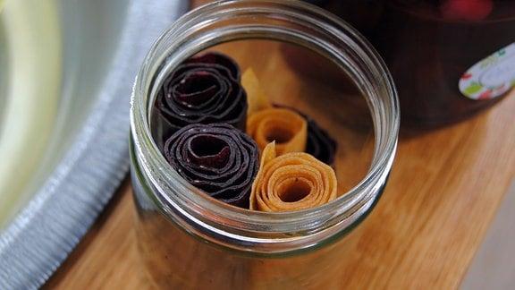 Aufgerolltes Fruchtleder aus Äpfeln und Schwarzen Johannisbeeren in Glas