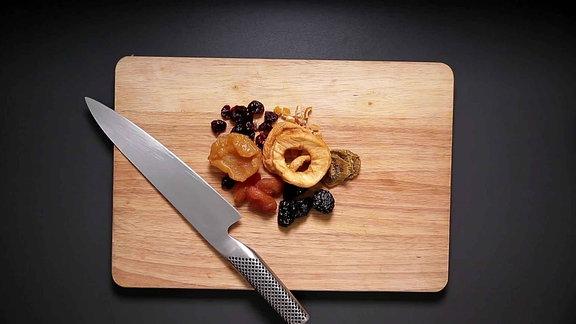 Trockenfrüchten auf einem Brett, daneben ein Messer