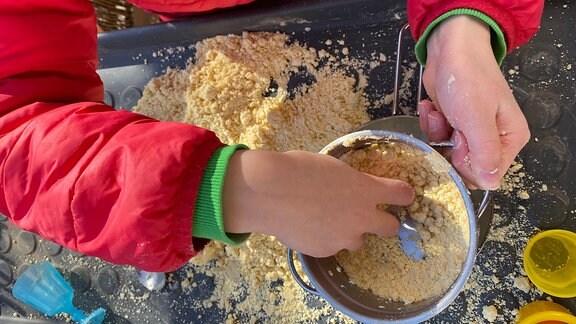 Kind spielt mit Sand-Ersatz während Coronavirus-Quarantäne