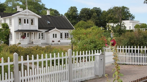 Ein weißes Gartenhaus mit einem weißen Zaun in der Kleingartenkolonie Landskrona in Schweden.