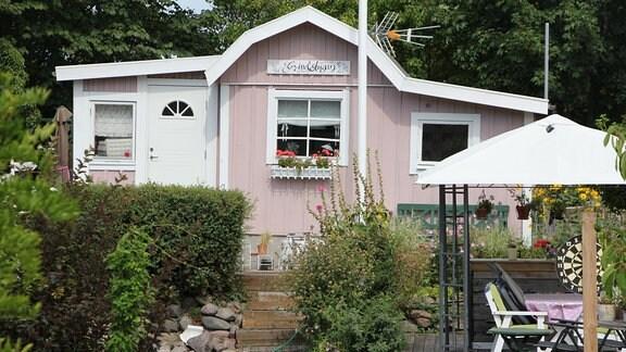 Ein rosa-weißes Gartenhaus mit Veranda in der Kleingartenkolonie Landskrona in Schweden.