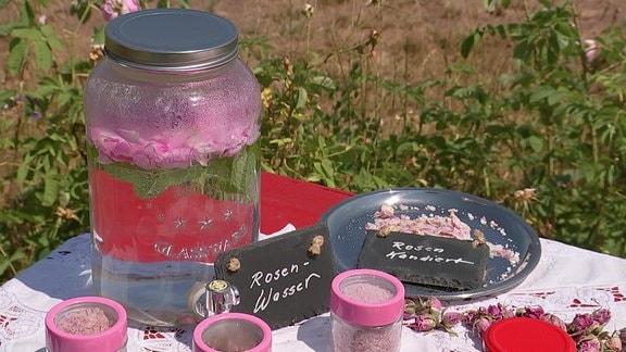 Auf einem Tisch stehen verschiedene Gefäße mit Lebensmitteln, die Rosenblütenblätter enthalten.