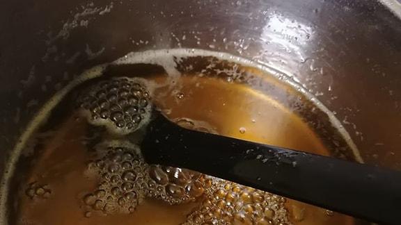 Goldgelber Sud Fichtenspitzen-Honig in einem Topf.