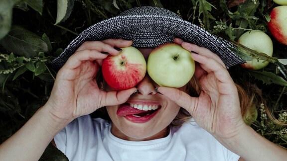 Ein Kind hält Äpfel vor seine Augen