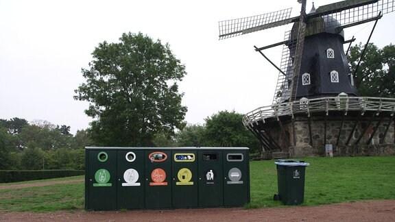 Öffentliche Müllcontainer in einem Park vor einer Windmühle in Malmö in Schweden.