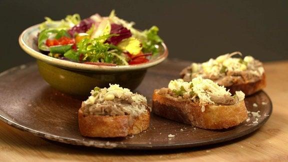 Eine Schüssel mit gemischtem Salat und drei Scheiben Weißbrot mit Aufstrich aus Bohnencreme