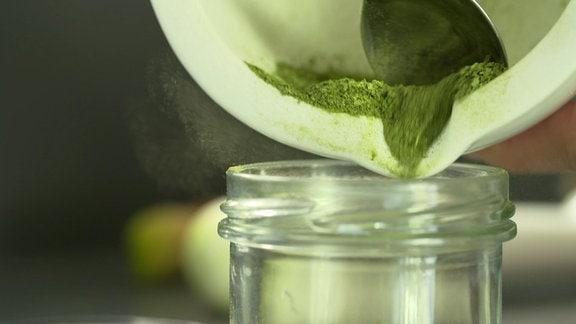 Grünkrautmehl wird in ein Schraubglas gefüllt.