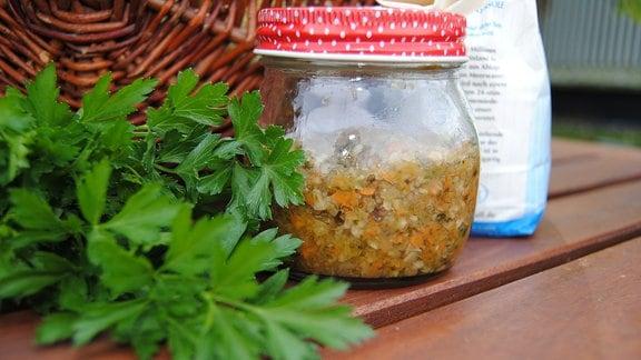 Bund glatte Petersilie neben einem Glas mit zerkleinertem Gemüse und Salz auf einem Holztisch
