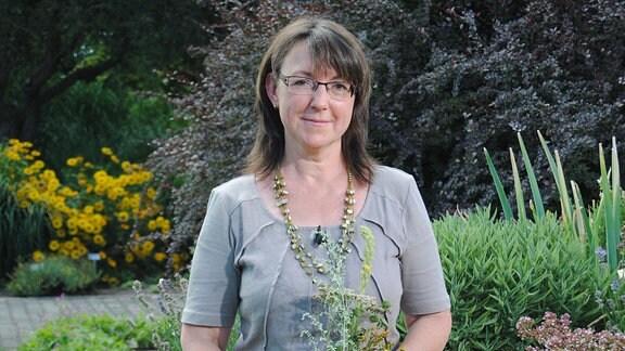 Die Kräuterfrau Ruth Bredenbeck steht mit einem Strauß Heilkräutern in den Händen vor einem Hochbeet mit Kräutern im egapark Erfurt