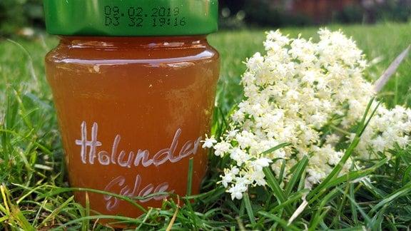 Auf einer Wiese steht ein Glas Hulunderblütengelee. Neben dem Glas liegt eine Holunderblüte.