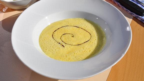 Ein Teller mit Kürbissuppe.